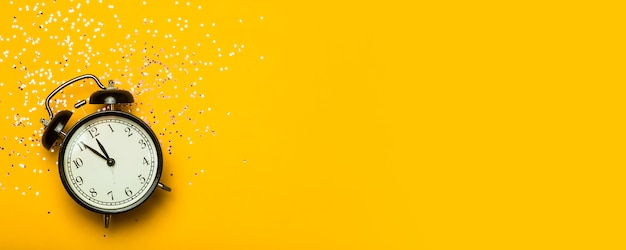Alarm clock on a yellow banner background with festive glitter. new year eve minimal background concept.