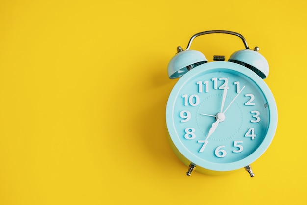 Alarm clock on yellow paper background