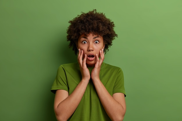緑の壁に隔離された、驚いた驚愕の暗い肌の女性が顔を掴み、息を止め、カジュアルな服を着て、何かを心配している。無言の感動した女性は信じられないほどのことを見る