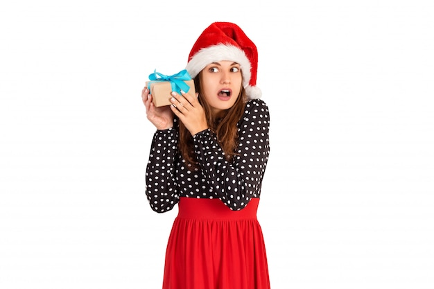 Alarmed girl with her gift listens to what's in the box. isolated on white . holidays