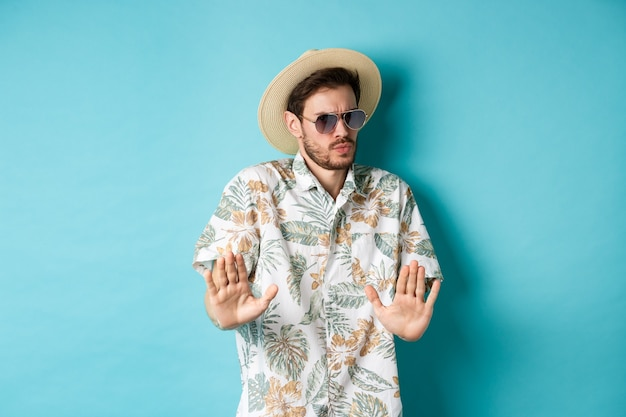 Alarmed tourist asking to stay away, step back from something cringe, showing rejection gesture, standing in straw hat and hawaiian shirt, blue background.