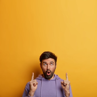 Alarmed worried unshaven man focused above with omg expression, dressed in purple sweatshirt, demonstrates big sales or unexpected offer, isolated over yellow wall. people and promotion