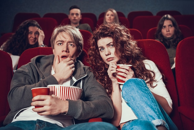 Alarmed young people with popcorn watch thriller at cinema