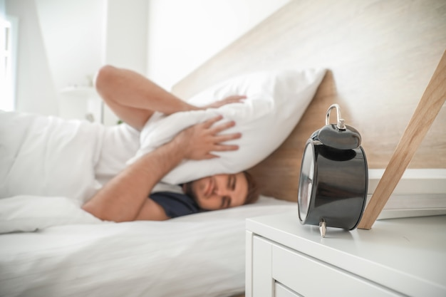 Alarming clock and young man covering head with pillow while trying to sleep in bed