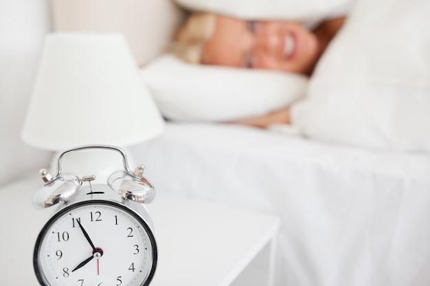 Alarrmclockが鳴っている間に枕に頭を隠している女性