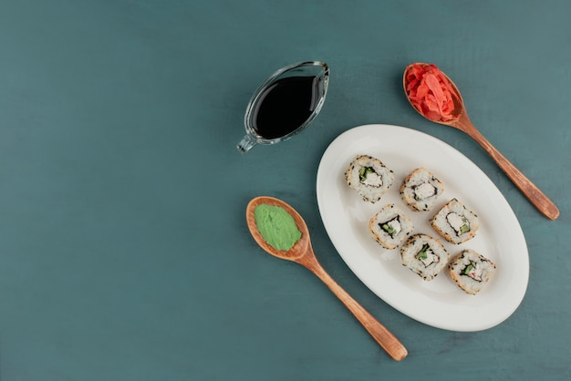 Alaska sushi roll on white plate with wasabi, pickled ginger and soy sauce.