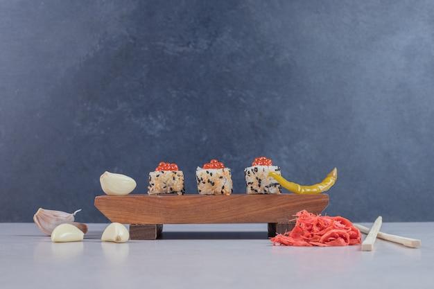 木の板に生姜のピクルスを添えたアラスカ巻き寿司。