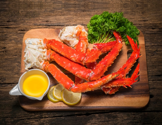 Alaskan king crab legs with butter and lemons on wooden space.