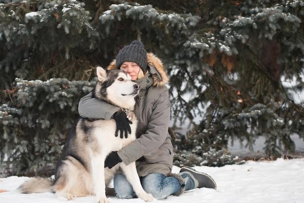 冬の森で女性と抱き締めるアラスカン・マラミュート。