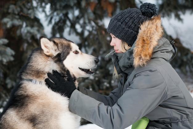 冬の森で女性とお互いを見つめるアラスカン・マラミュート