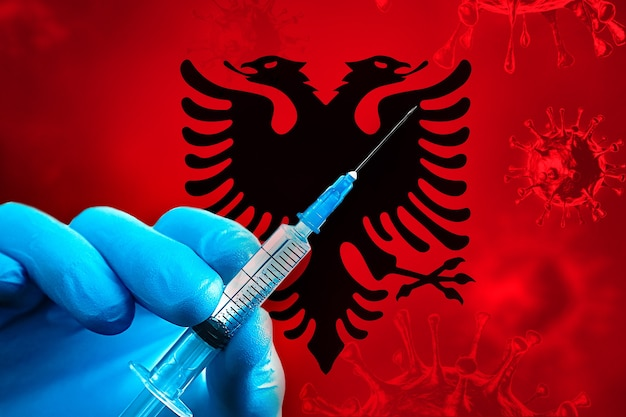 알바니아 covid19 예방 접종 캠페인 파란색 고무 장갑을 끼고 깃발 앞에 주사기를 들고 있습니다.