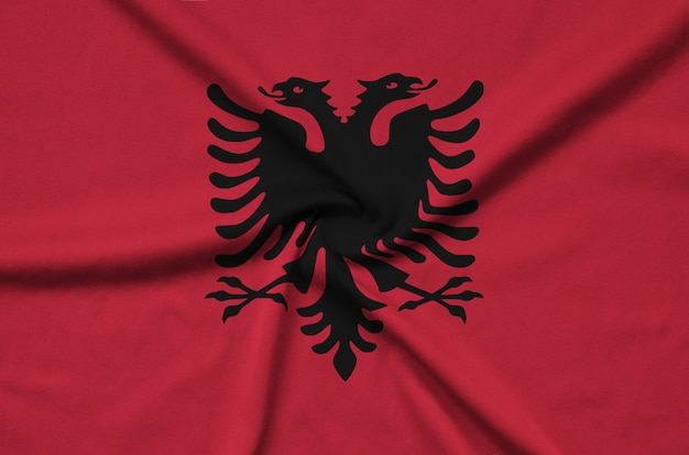 Albania flag  is depicted on a sports cloth fabric with many folds.