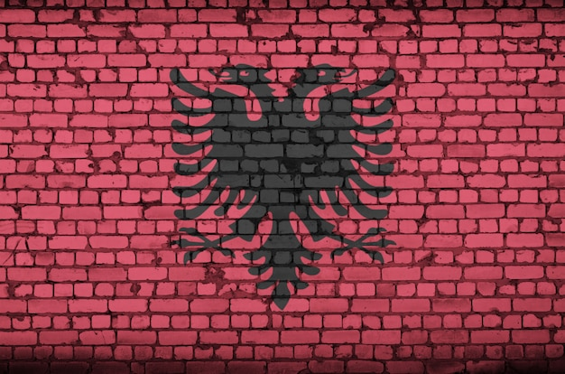 Albania flag is painted onto an old brick wall