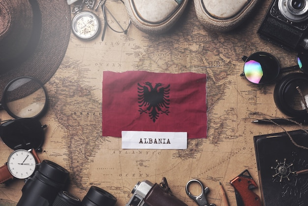 Albania flag between traveler's accessories on old vintage map. overhead shot