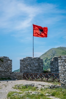 Albanian red flag with a black double-headed eagle towers above the fortress of rozafa.