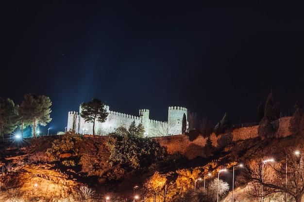 Замок альберге-кастильо-сан-сервандо освещается ночью, толедо, испания