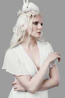 Albino blond woman in elegant dress posing with cute little rabbit