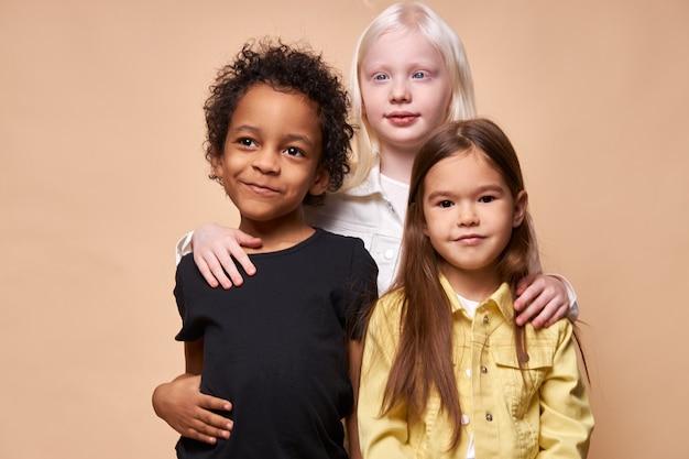 アルビノの女の子は若い友達、アフリカ系アメリカ人の男の子と白人の女の子を抱きしめます