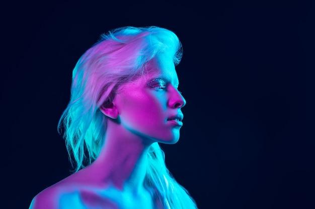 Девушка-альбинос с белой кожей, естественными губами и белыми волосами в неоновом свете, изолированные на черном фоне студии.