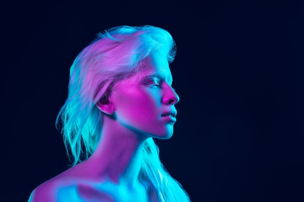 Albino girl with white skin, natural lips and white hair in neon light isolated on black studio background.
