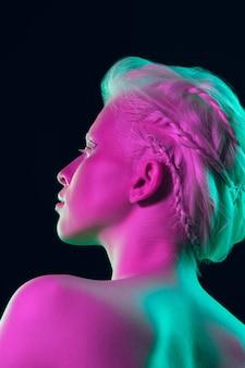 Ragazza albino con pelle bianca, labbra naturali e capelli bianchi in luce al neon isolata su sfondo nero studio.