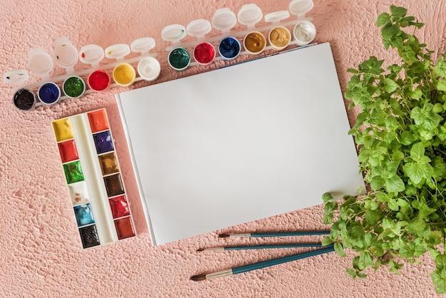 Альбом и краска для рисования на розовом фоне