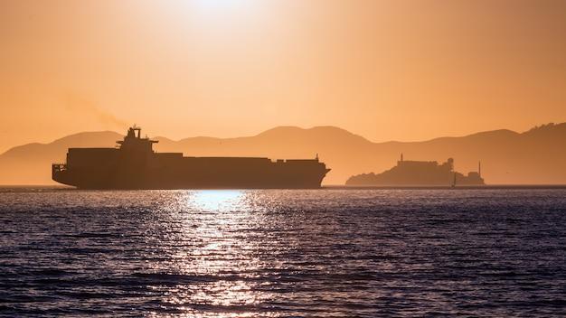 Alcatraz island penitentiary at sunset and merchant ship