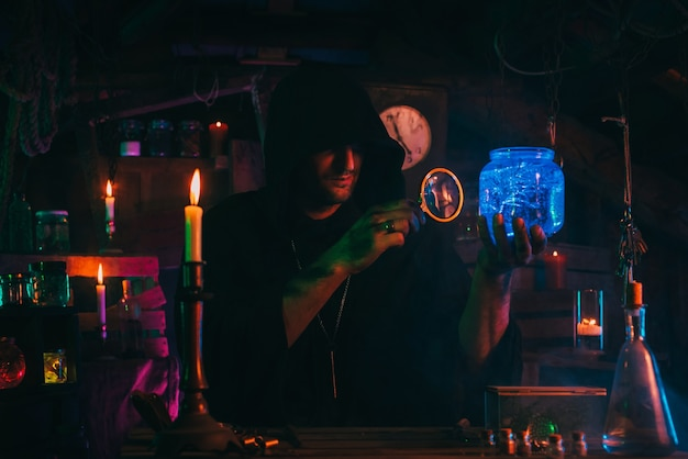 Alchemist magician holds a flask with a mystical potion in hands. sorcerer is witcher in dark scary laboratory