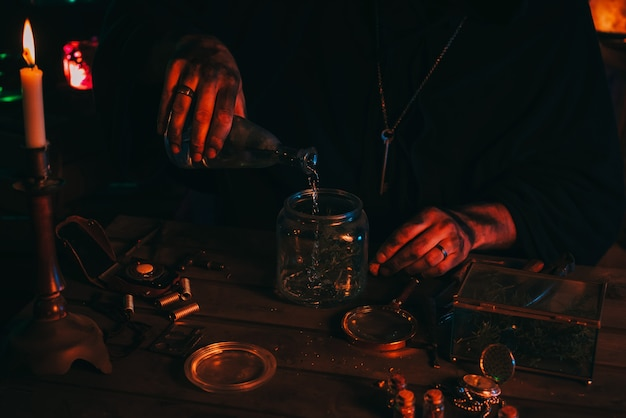 Alchemist magician sorcerer does experiments with a potion in a laboratory with herbs and glass flasks