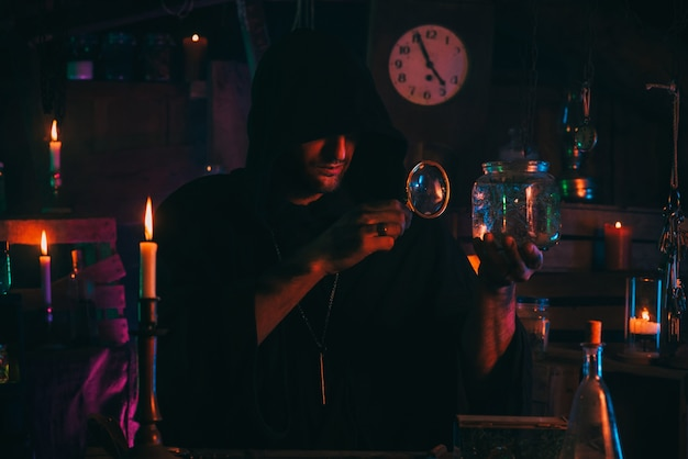 Alchemist magician sorcerer does experiments with a potion in a laboratory