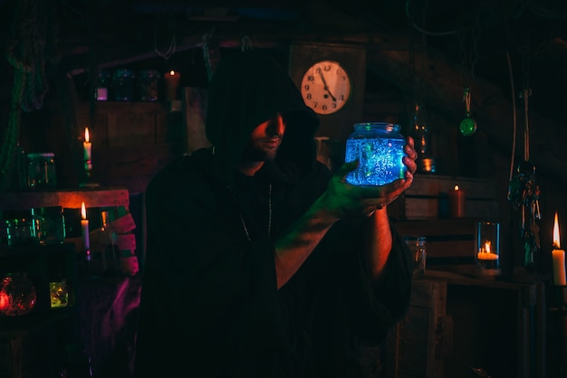 Alchemist sorcerer with a flask of magic potion in hands in terrible workshop. witcher magician in a halloween costume