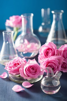 バラの花とケミカルフラスコ入りの錬金術とアロマセラピー