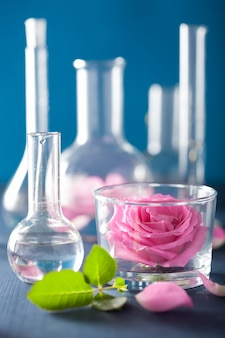 Alchemy and aromatherapy set with rose flowers and chemical flasks