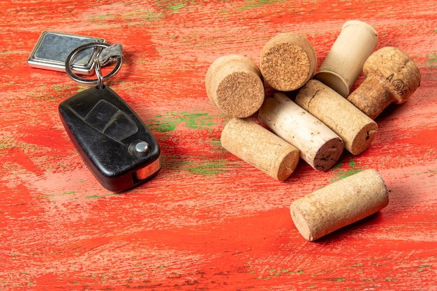 Alcohol abuse and danger in car driving symbolized by key and cork