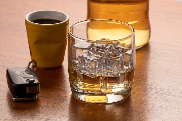 테이블에 얼음과 자동차 키가 있는 위스키 한 잔으로 알코올 남용.