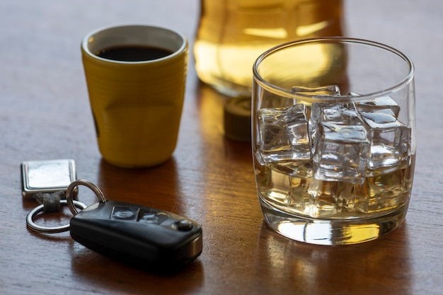 Alcohol abuse with glass of whiskey with ice and car key on the table.