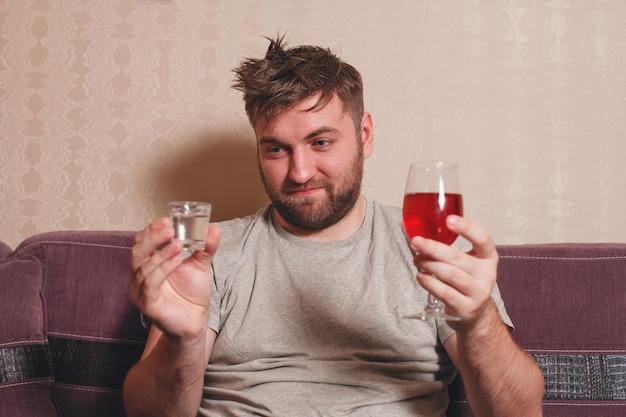 アルコール中毒の男性は二日酔いのために飲み物を選ぶ