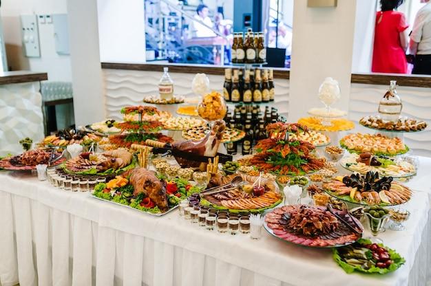 술과 음식. 테이블에 스낵과 함께 맥주입니다. 화창한 날 나무 테이블에 있는 그릴에서 요리된 다양한 음식, 가재, 오징어, 해산물, 칩, 견과류. 실내 음식 개념입니다.