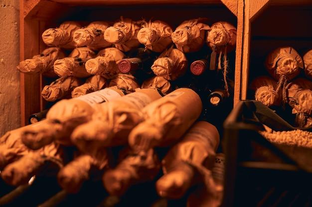 Хранение алкогольных напитков. ряды винных бутылок, завернутых в крафт-бумагу, лежат на полках