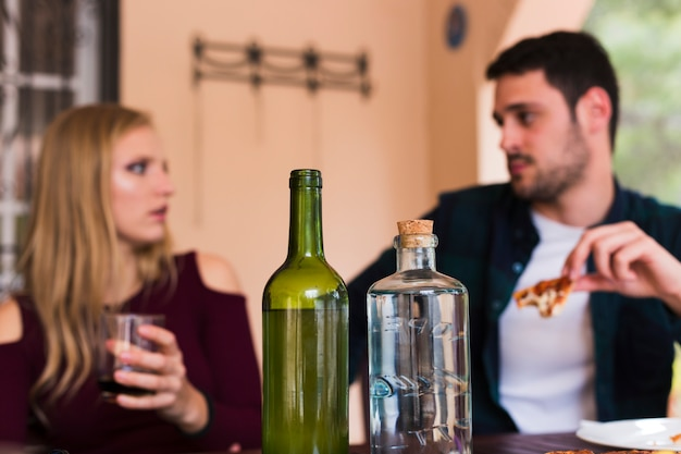 Alcohol bottle in front of couple eating food