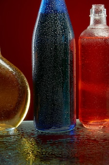 Alcohol bottles in water drops on red