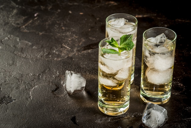 Alcohol cocktail made from golden tequila with ice cubes and mint. on a black concrete table. copy space