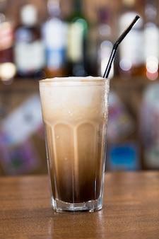 Алкогольный коктейль на деревянной барной стойке с барной стойкой