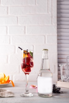 Alcohol cocktail with fresh fruits and berries with a bottle of tonic