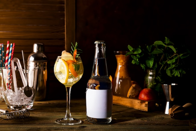 Alcohol cocktail with fresh fruits and with a bottle of tonic  on wooden background