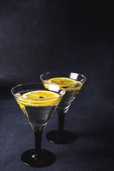 Алкоголь коктейль с всплеск. сухой мартини с черными оливками. вермут коктейль внутри мартини стекла на темном фоне. бокалы для мартини находятся на панели.