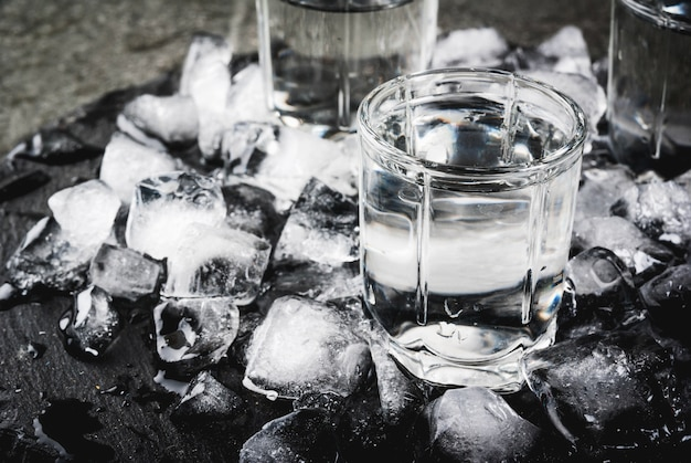 Alcohol and cocktails. three glasses of vodka on a slate tray, with ice. on a black stone table,  top view
