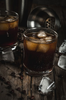 Alcohol. drinks, boozy black russian cocktail with vodka and coffee liquor on rustic wooden table. copy space