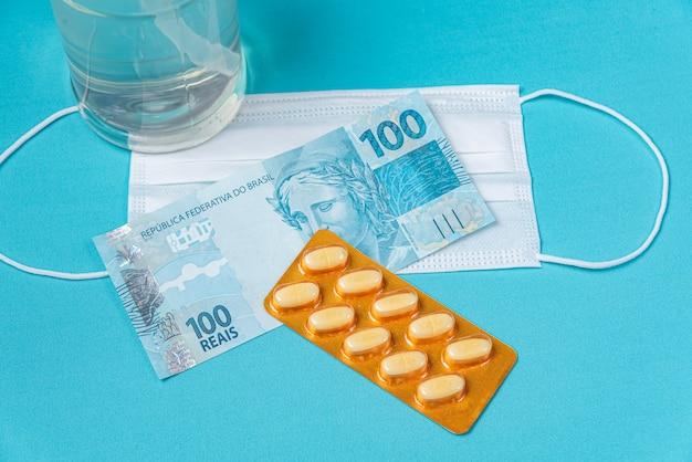 アルコールジェルコンテナ、サージカルマスク、薬、ブラジルのリアルマネー、