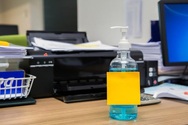 紙のノートが付いている机の上のアルコールゲル。コンセプトは、コロナウイルスまたはcovid-19から保護するために消毒剤を使用します。